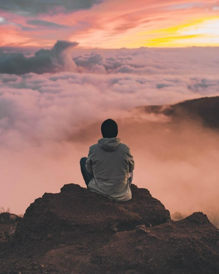 man looking in the distance above the clouds