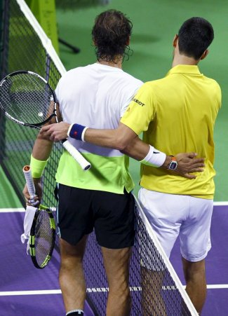 Novak Djokovic of Serbia (R) walks with Rafael Nadal of Spain after their Qatar Open men's single tennis final match in Doha, Qatar, January 9, 2016. REUTERS/Ibraheem Al Omari