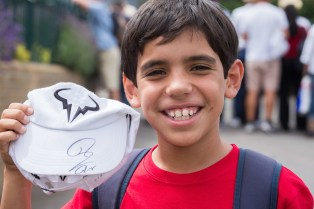 A young fan shows his excitement after getting his merchandise signed by the players. The Championships 2017 at The All England Lawn Tennis Club, Wimbledon. Credit: AELTC/Roger Allen.