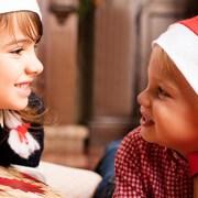 Dos nens amb barrets de Pare Nadal i amb regals,
