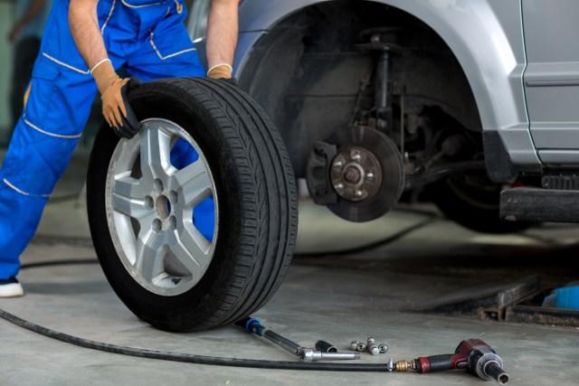 mechanic changing wheel of a modern car