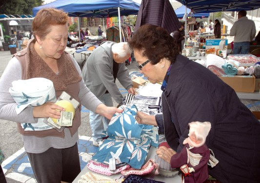 Actress Amy Hill makes a purchase of some vintage Japanese fabrics, to go along with her various other finds. (Mikey Hirano Culross/Rafu Shimpo)