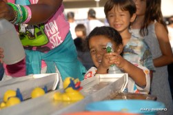 Games for kids included this one involving rubber duckies and squirt guns. (MIKEY HIRANO CULROSS/Rafu Shimpo)