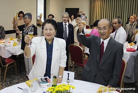10周年を記念し乾杯する平山さん(左)と、二人三脚でラジオ放送を支えてきた夫の安正さん