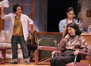 """In a scene from """"Steel Magnolias,"""" Annelle (Lovelle Liquigan) does Clairee's (Dian Kobayashi) hair while Ouiser (Karen Huie) complains about church mailings she has been receiving. (Photo by Michael Lamont)"""