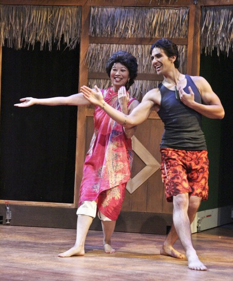 """Jeanne Sakata as Tomi gets a hula lesson from Kimo, played by Tui Asau, in East West Players' """"The Nisei Widows Club: How Tomi Got Her Groove Back."""" (Photo by Michael Lamont)"""