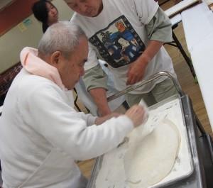 George Yamada shows how to shape freshly pounded mochi.