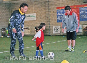 Tampa Bay Rowdies defender Takuya Yamada, left, and assistant coach Ryota Suzuki encourage a young Lezele player.