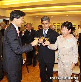 新美総領事(左)と乾杯する半田夫妻