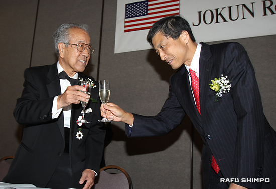 新美総領事(右)と乾杯する受章者の中村さん