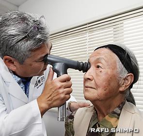 検眼鏡を使い吉川さん(右)を診察するクラタ医師