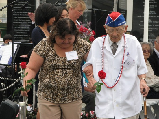 Mits Kunihiro and his daughter Linda prepare to place flowers on the monument.