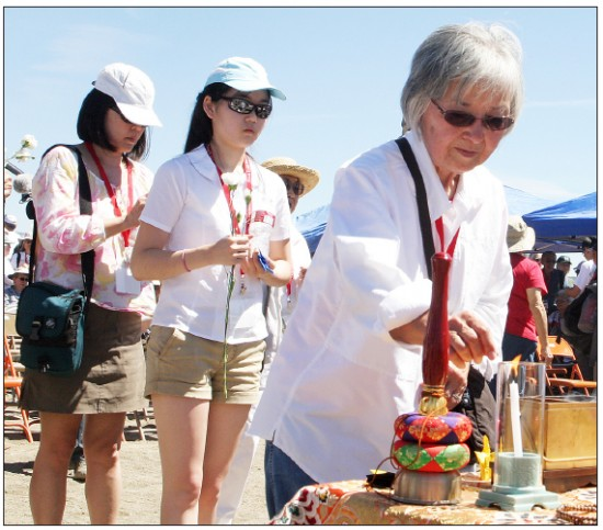 Mabel Imai Tomita gives an offering of incense at this year's Tule Lake Pilgrimage. The loyalty questionnaire caused a split in her family that took years for her to discover. (Photo by Martha Nakagawa)
