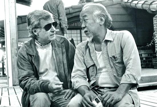 "Director John Avildsen and actor Pat Morita talk during the filming of ""The Karate Kid Part II."""