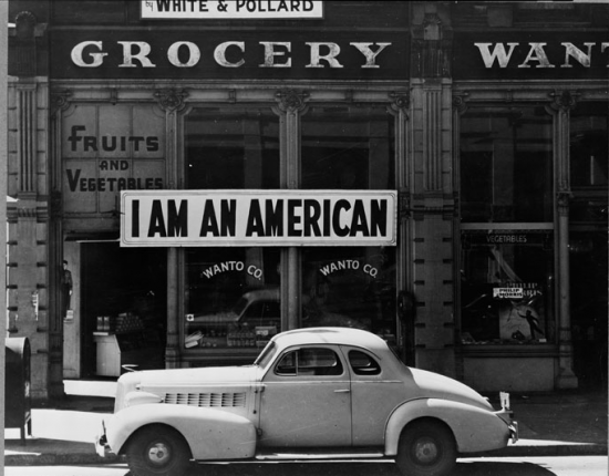 """Oakland, March 1942. A large sign reading """"I am an American"""" placed in the window of a store at 13th and Franklin Streets on Dec. 8, the day after Pearl Harbor. The owner, a University of California graduate, was among the Japanese Americans removed from the West Coast. (Dorothea Lange for U.S. War Relocation Authority)"""