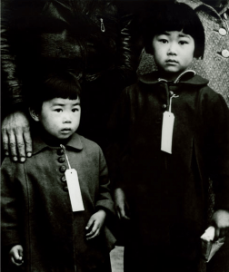 """Hayward, Calif., 1942. All Japanese American """"evacuees"""" were required to wear identification tags. (Dorothea Lange for U.S. War Relocation Authority)"""