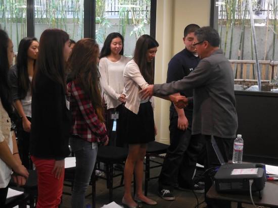 John Kobara teaches Teia Noel the art of the handshake as part of the networking workshop.