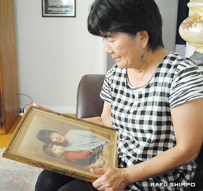 一番お気に入りのトクさんとの写真を見つめるナカムラさん
