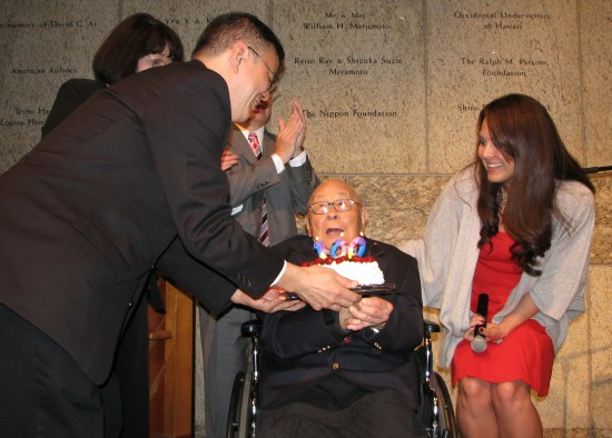 Fred Hoshiyama receives a birthday cake from his son Matthew. At right is singer Lauren Kinkade, Hoshiyama's cousin's granddaughter.