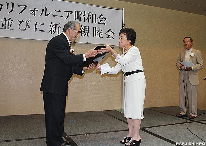 山口新会長(右)から記念品を手渡される小山前会長(左)