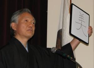 """Consul General Harry Horinouchi showed how the kanji for """"sheep"""" (hitsuji) can be changed into the kanji for """"beautiful"""" (utsukushii)."""