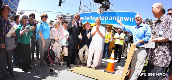 A crowd cheers as the Sawtelle Japantown sign is unveiled on Sunday. Among those joining in the ceremony are Randy Sakamoto (right) of the Sawtelle Japantown Association, Councilmember Mike Bonin (second from left), and Consul General Harry Horinouchi (left of sign).