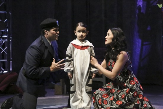 """Capt. Walker (Cliffton Hall) and Mrs. Walker (Deedee Magno Hall) try to convince 4-year-old Tommy (Araceli Prasarttongosoth) that he did not see or hear the murder that just took place in the East West Players production of """"The Who's Tommy.""""  (Photo by Michael Lamont)"""