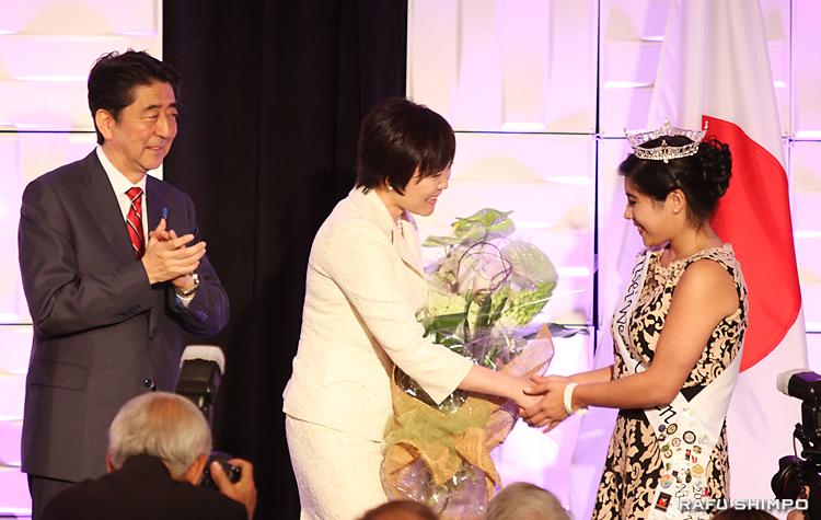 昼餐会で、二世週祭女王のトーリ・ニシナカ―レオンさん(右)から花束を贈られる安倍昭恵・首相夫人。左は拍手を送る安倍首相