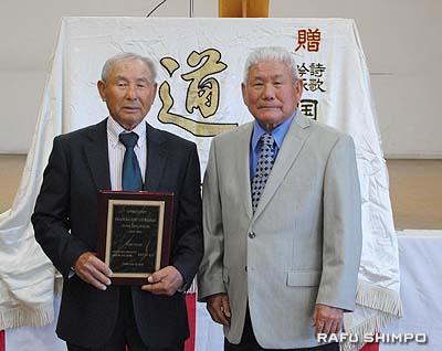 仁田尾国康師範(右)から感謝の盾を授与された岡村前地区理事長