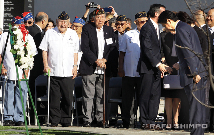 As Japanese American veterans of World War II look on, Prime Minister Abe and his wife (obscured) bow before a wreath the Japanese leader placed at the Go For Broke Monument in Little Tokyo. Abe spent several minutes chatting with the former soldiers during the visit. (MARIO G. REYES/Rafu Shimpo)