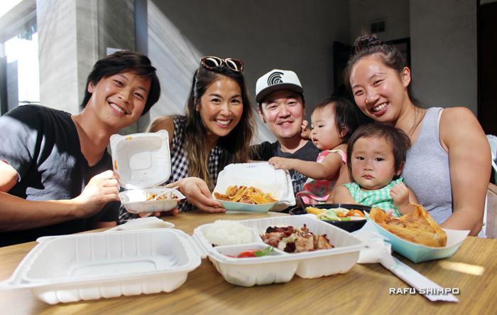 リサイクルできる容器に入ったテリヤキやタマレを楽しむ家族とその仲間たち