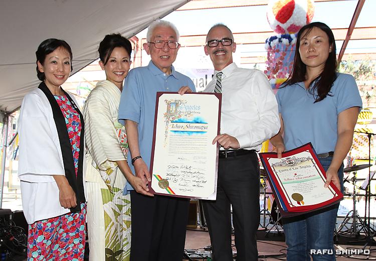 ロサンゼルス市から贈られた表彰状を披露する白松さん(左から3人目)。右端が撫養委員長