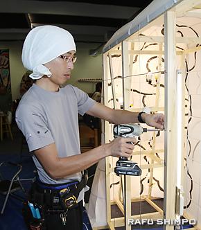 木枠に針金を付けるためのネジを取り付ける三浦圭さん