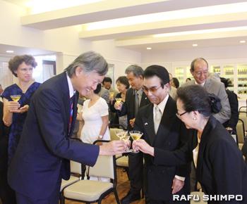 堀之内総領事(左)と乾杯する比嘉氏(中央)と妻の博子さん(右)