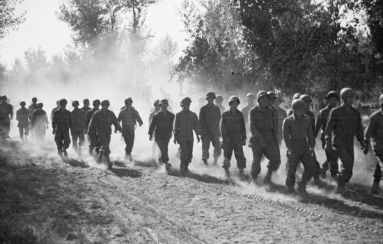 Photo by Sus Ito of soldiers of the 522nd Field Artillery Battalion marching along a dirt road in Naples, Italy, May 1944.