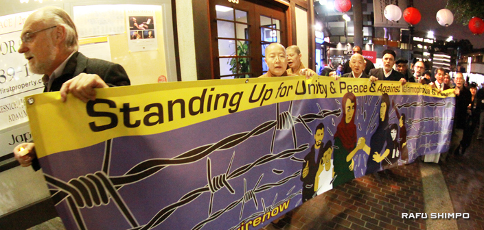 Vigil participants carry a banner as they walk from JACCC through Japanese Village Plaza to JANM. (MARIO G. REYES/Rafu Shimpo)