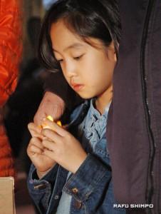 Naiya Kim holds a candle during the vigil. (MIKEY HIRANO CULROSS/Rafu Shimpo)
