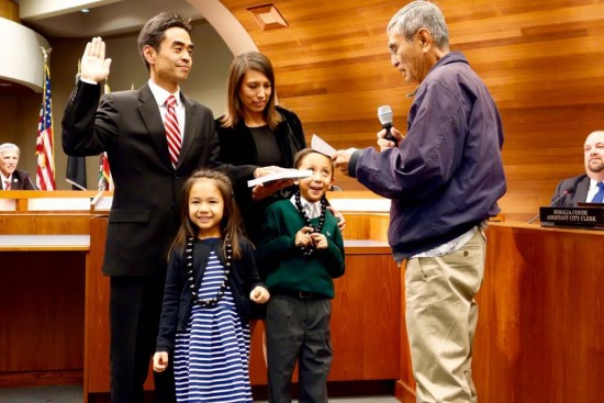 Accompanied by his wife, Minerva, son, Cruz, and daughter, Paz, James Toma is sworn in as mayor of West Covina by his father, Walter.