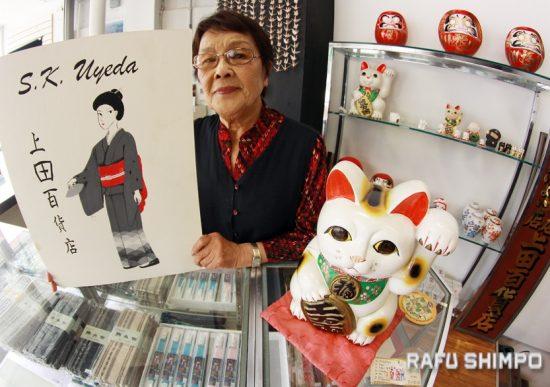 Tsuyako Kunishige, who has worked at S.K. Uyeda for 27 years, with some of the store's specialties, including maneki-neko and drama.