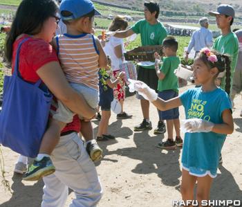 参加者に新鮮な野菜を配るボランティアの女の子