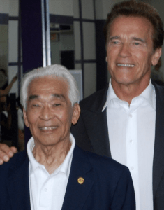 Tommy Kono poses with Gov. Arnold Schwarzenegger at Sacramento High School in August 2010. (Courtesy Hassle Free Barbell Club)