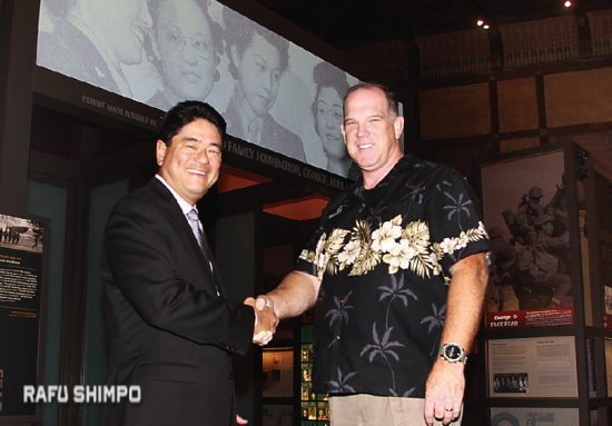 Vince Beresford, outgoing Go For Broke president and CEO, shakes hands with Mitch Maki, interim president and CEO on Wednesday. (MARIO G. REYES/Rafu Shimpo)