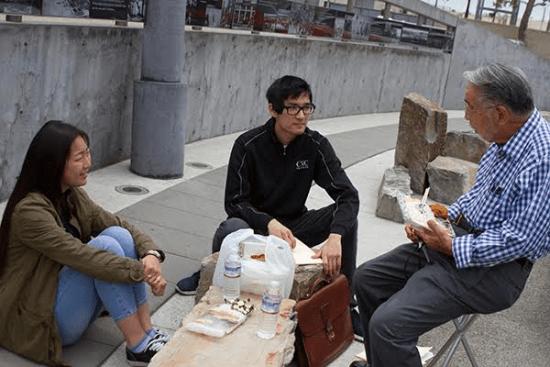 Minoru Tonai chats with Tuna Canyon Detention Center college interns Ariel Imamoto and Keith Matsushita at the Terminal Island Japanese Memorial. (Photo by Nancy Hayata)