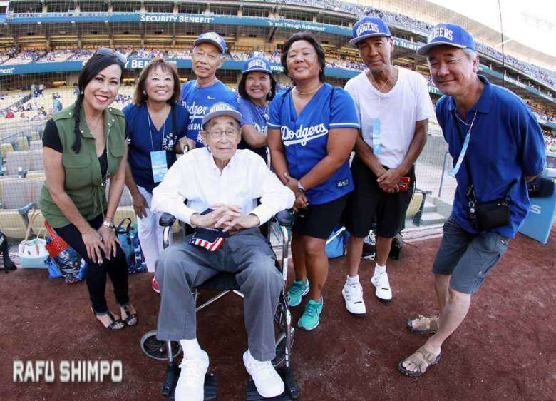 From left: Military Hero of the Game Jack Kunitomi (seated) is joined on the field by (from left) Susan Hirasuna of Fox 11, daughter Kerry Cababa, son Dale Kunitomi, daughter Colleen Miyano, granddaughter Claudine Cababa, son Donald Kunitomi, and son Darrell Kunitomi. (MARIO G. REYES/Rafu Shimpo)