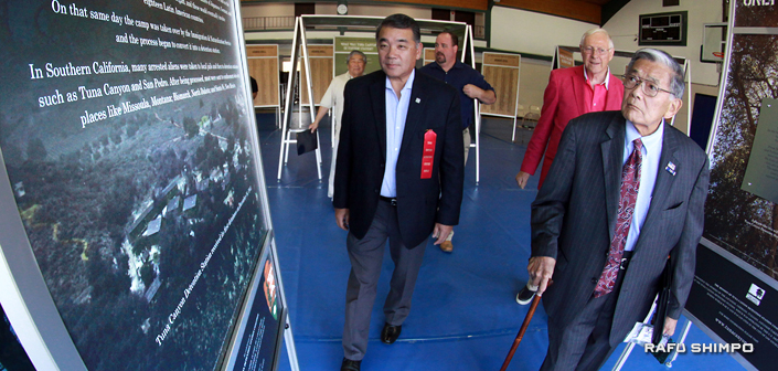 """Former Secretary of Transportation Norman Mineta (right) and Los Angeles County Supervisor Mike Antonovich are given a tour of """"Only the Oaks Remain"""" by former LAPD Deputy Chief Terry Hara."""