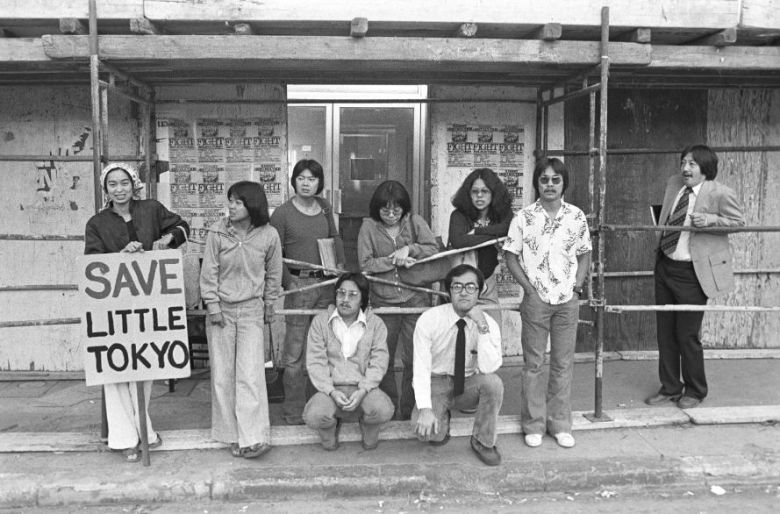 Members of the Little Tokyo Peoples' Right Organization are seen picketing in front of one of the storefronts on Weller Street slated for demolition, circa 1977. Pictured from left: Joanne Sakai, Lucien Kubota, Alan Kondo, Dean Toji, Evelyn Yoshimura, Bruce Iwasaki, Qris Yamashita, Duane Kubo, and Mike Murase. (Visual Communications Photographic Archive)