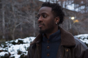 nana kwame stands in profile outdoors by snowy bushes