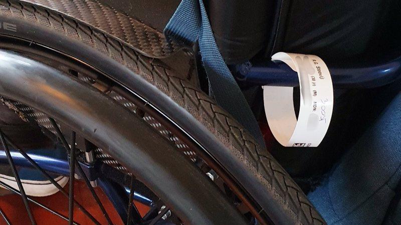 Polsbandje voor de operatie in het ziekenhuis vastgemaakt aan mijn rolstoel