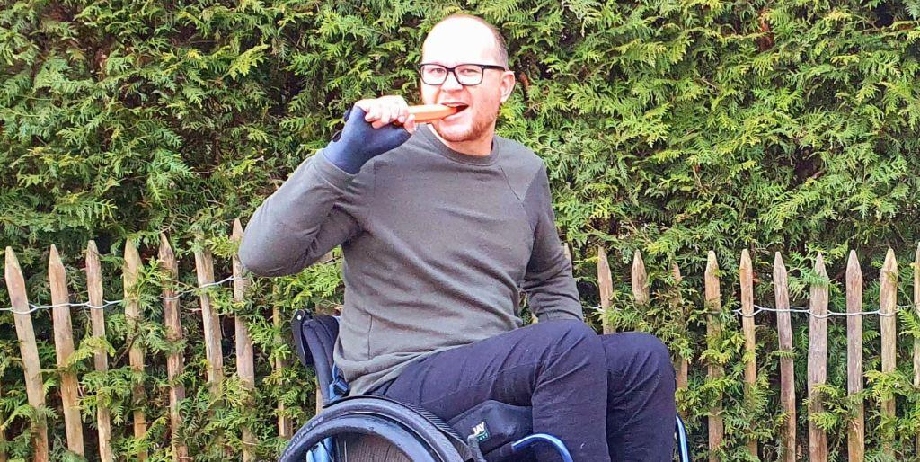 foto van een rolstoelgebruiker die een hap van een wortel neemt en daarmee aangeeft hoe gek het is als je ongevraagd een worteldieet aan een brilgebruiker adviseert