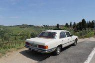 foto van een klassieke oldtimer van Mercedes-Benz W116 in de heuvels van Toscane met op de achtergrond wijngaarden